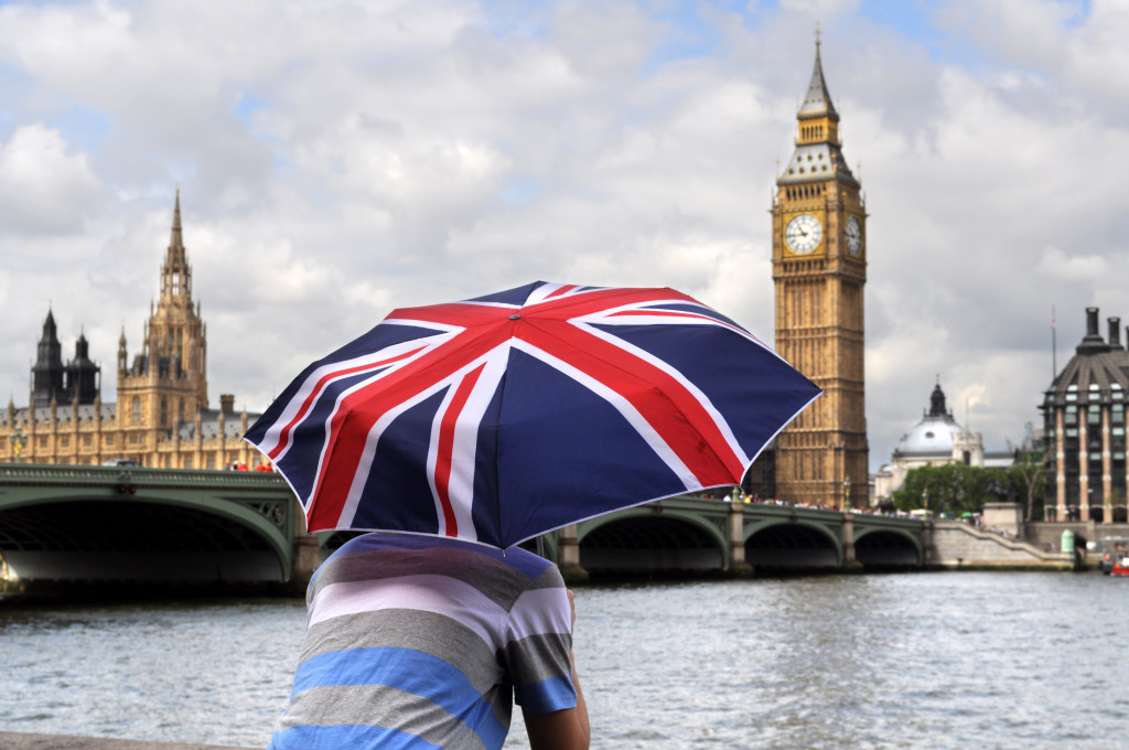Big Ben and tourist with British flag umbrella in London